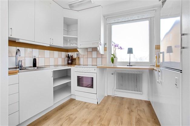 Fräscht kök med vit inredning. Här finns ett fönster som ger köket mycket ljusinsläpp.