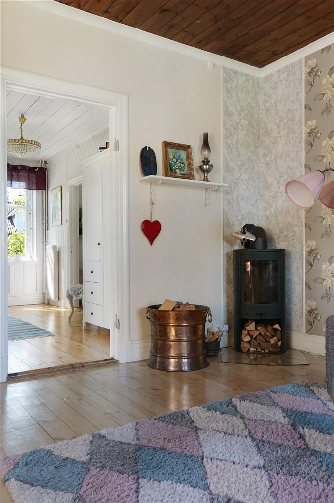 Vardagsrum med burspråk, trägolv, tapetserad fondvägg samt en kamin.