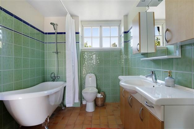 Badrum med kaklade väggar och eluppvärmt klinkergolv, badkar, toalett, tvättställ i kommod och fläkt.