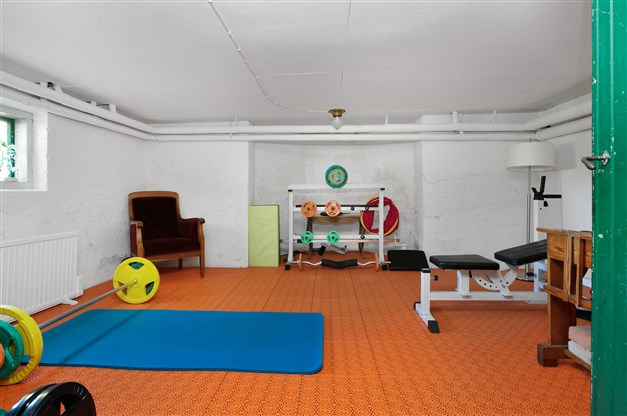 Rum med vitputsade väggar och betonggolv under golvplattor av plast.