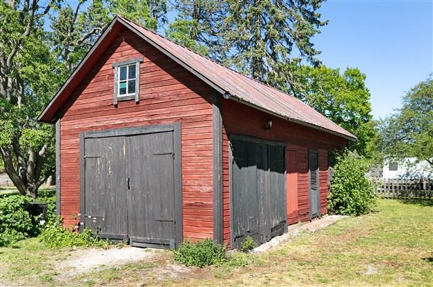 Lada med gjutet golv, träfasad, plåttak och garageport.