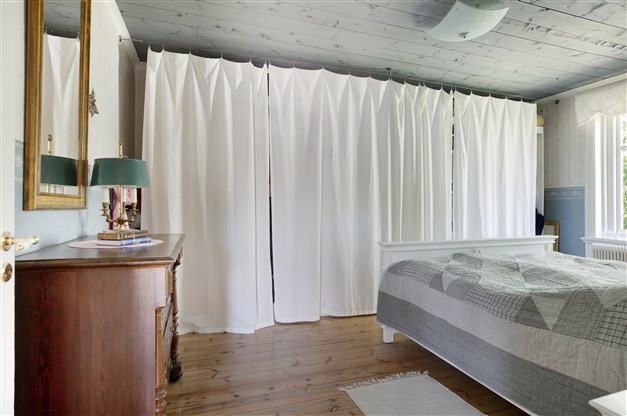 Sovrum med trägolv och garderobsförvaring bakom draperier.