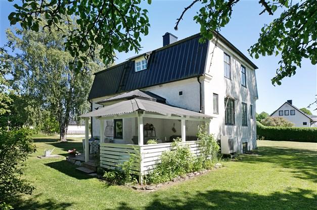 Trälagd altan delvis under tak på husets baksida samt en balkong över veranda på framsidan.