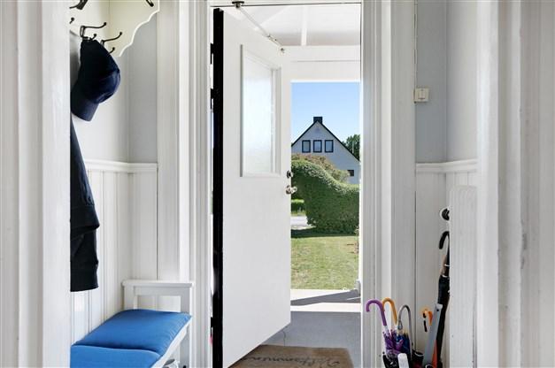 Entré med bröstpanel på väggar, trägolv under löst liggande textilmatta samt plats för avhängning.