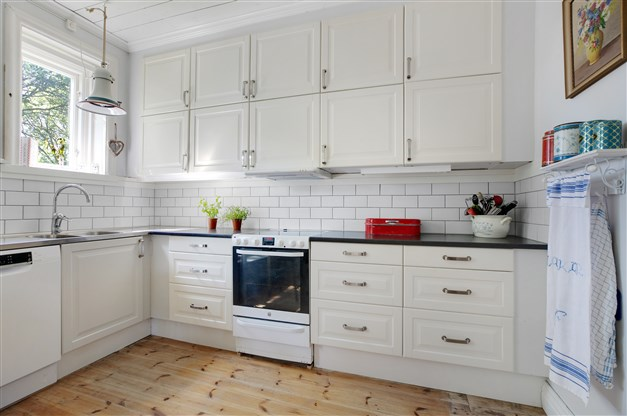 Kök med spis med induktionshäll och varmluftsugn, fläkt, diskmaskin och kombinerad kyl/frys