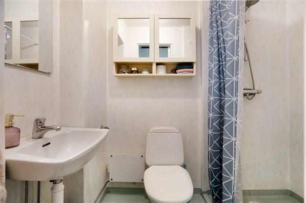 Duschrum med våtrumsmatta på väggar och golv. Utrustning: dusch, fläkt, toalett och tvättställ.