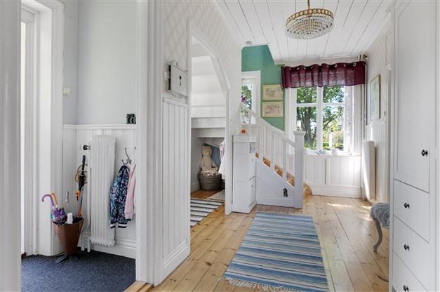 Hall med trägolv, bröstpanel/tapet på väggar och trappa till ovanvåningen.