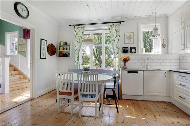 Kök med trägolv, ljus köksinredning, stänkskydd av vitt kakel samt matplats intill fönster.