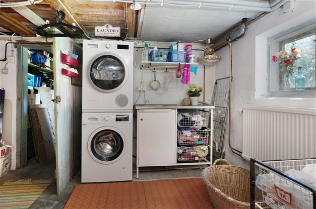 Tvättstuga med betonggolv och putsade väggar. Utrustning: tvättmaskin, torktumlare och tvättbänk med ho.