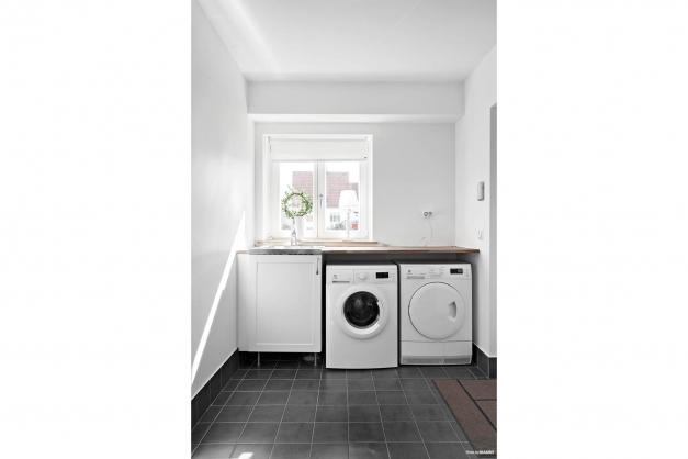 Rymlig tvättstuga med tvättmaskin och torktumlare.