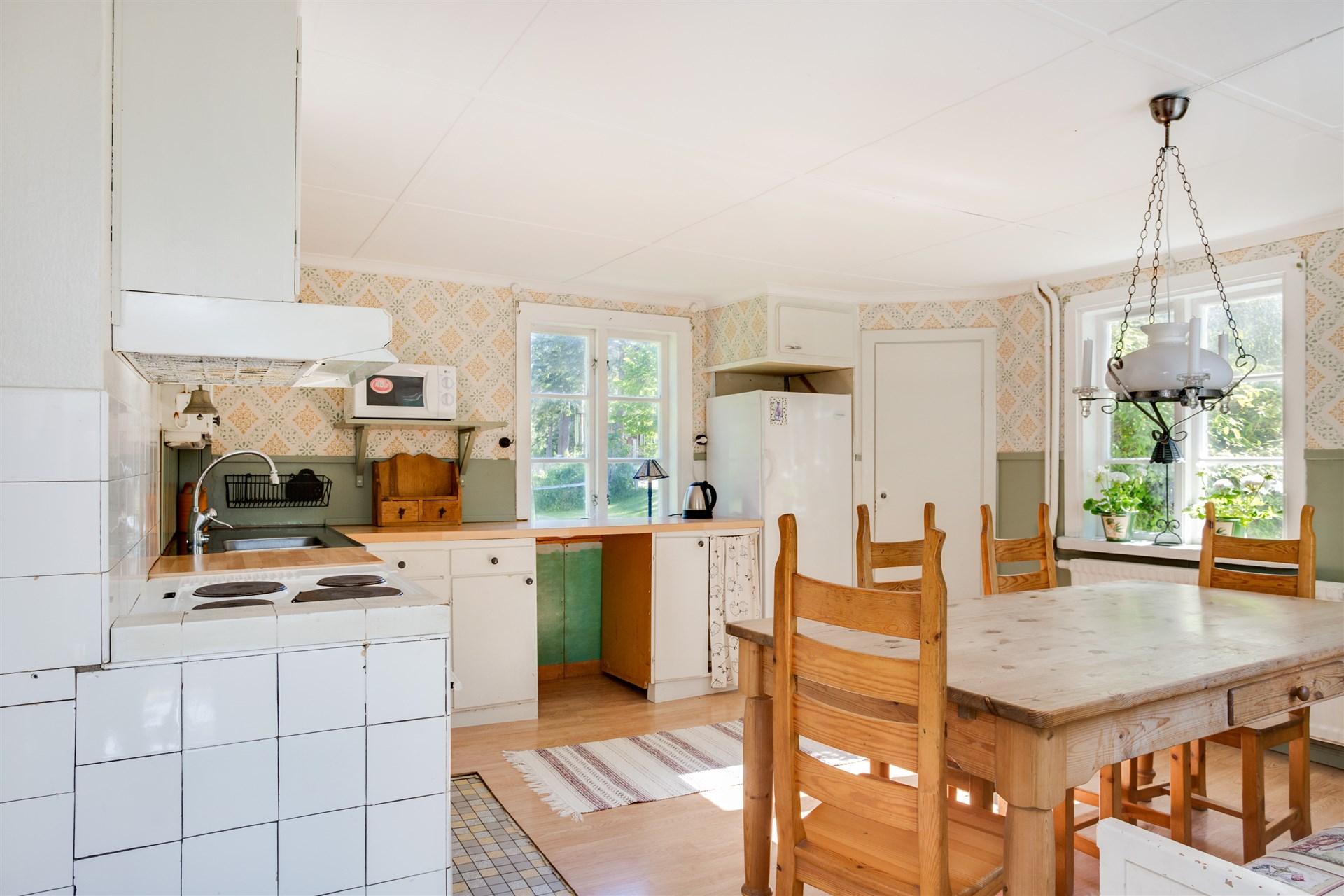 Mysigt kök i gammal stil med fönster åt tre håll.