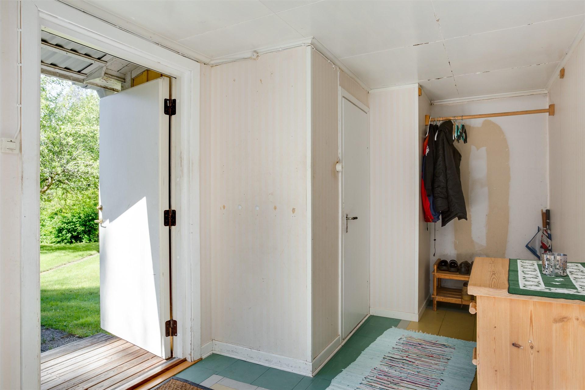 Välkommen in! Ljus hall med plats för kläder och ingång till dusch/wc.