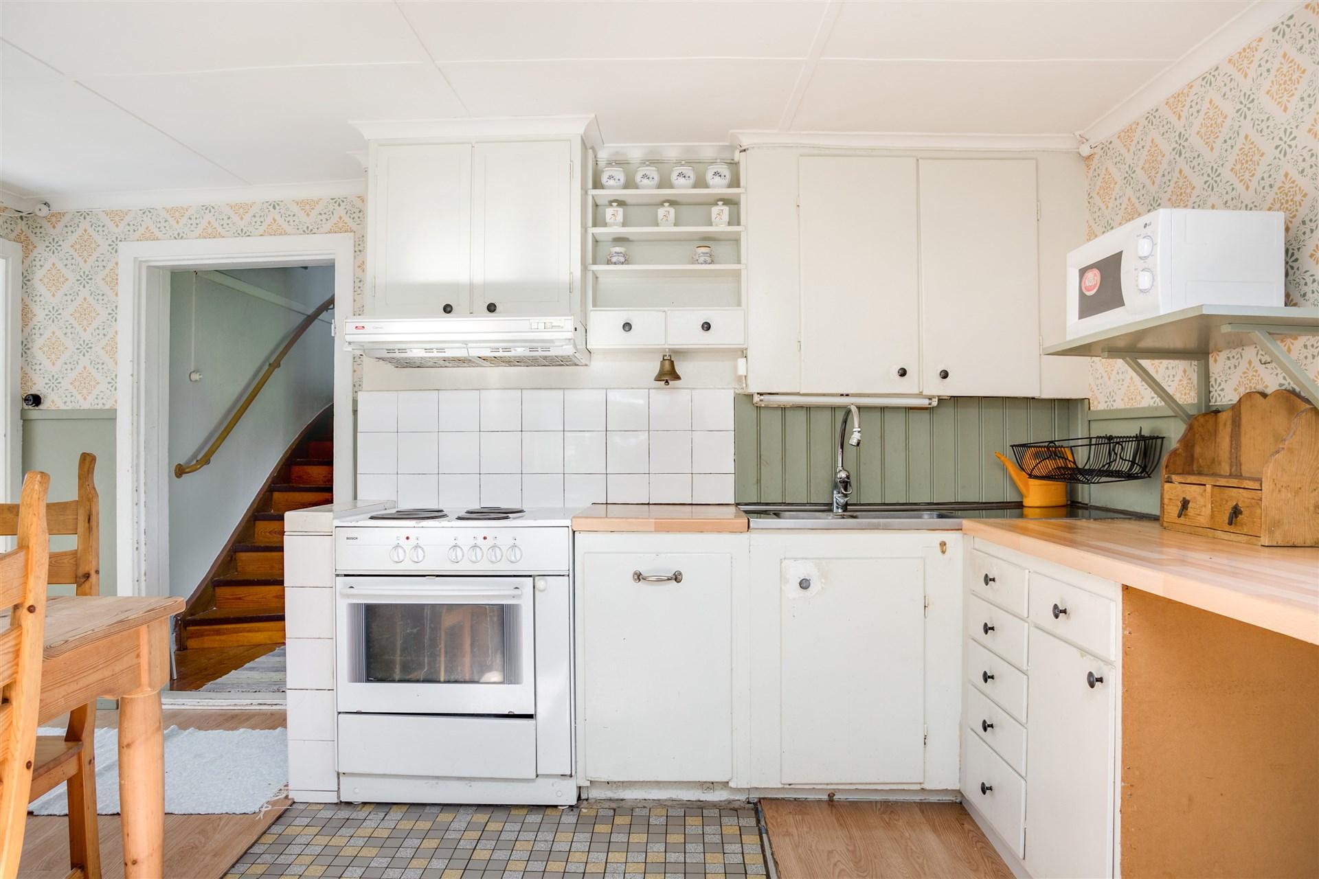 Köket har vita köksluckor och stora arbetsytor.
