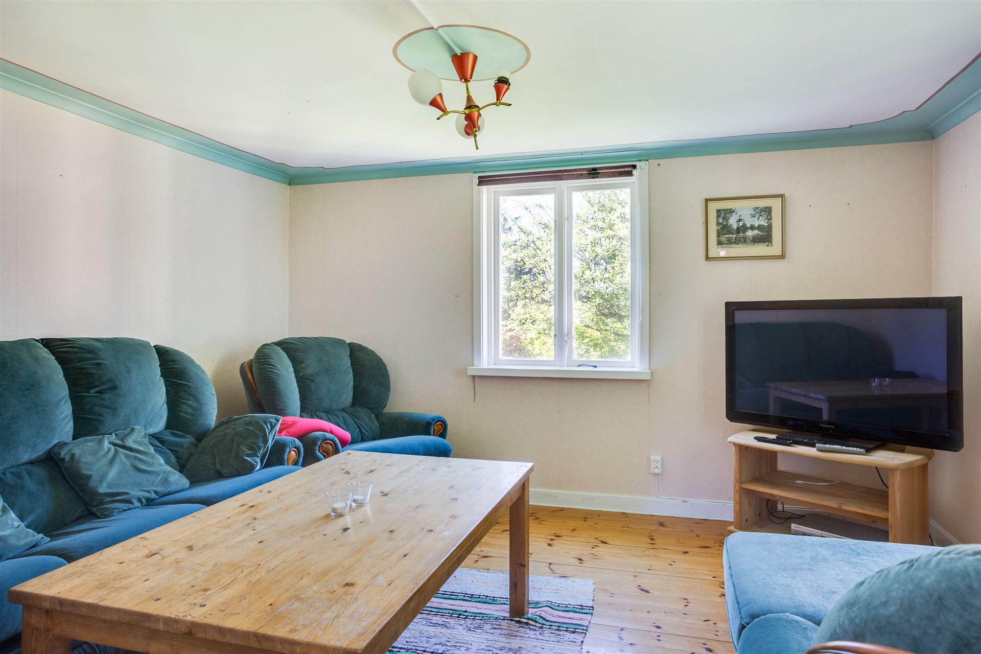 Litet och mysigt vardagsrum med trägolv.