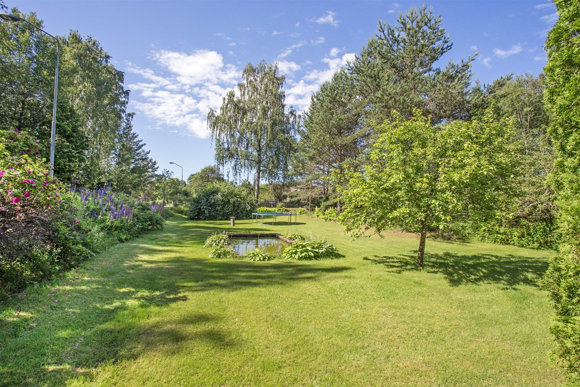 Lummig och fin trädgårdstomt med buskar, träd, blommor och en damm.