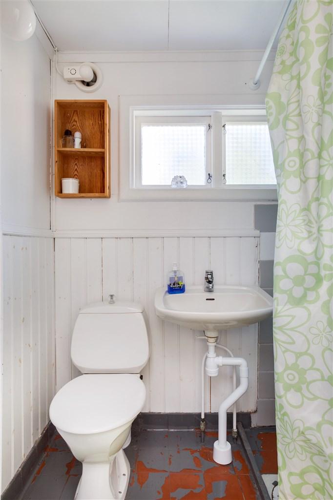 Dusch/wc med klinker på golv och bröstpanel/målad vägg. Här finns wc, handfat och dusch.