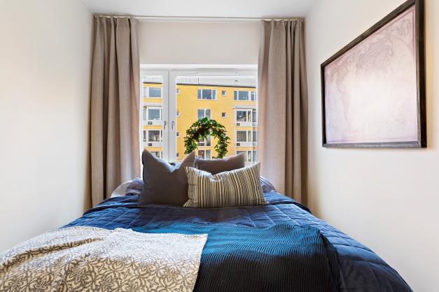 Sovrum med plats för bred dubbelsäng. Lungt mot gården.