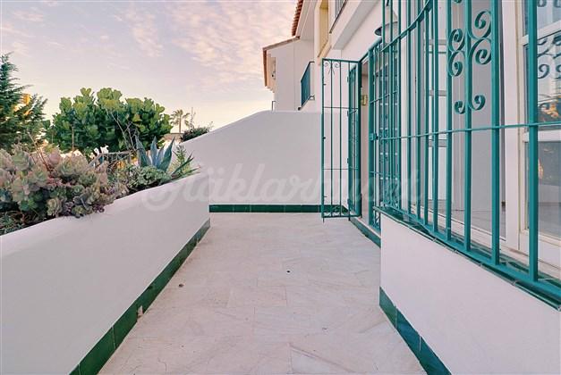 Terrass med trappa ner till den gemensamma trädgården och poolområdet