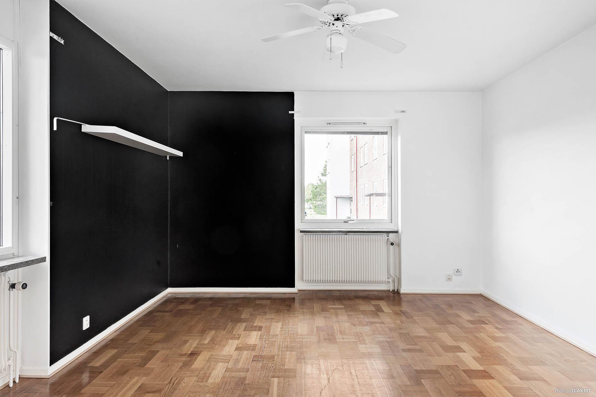 Vardagsrummet, med målad vägg. Lättmöblerade ytor med plats för både soffa och media.