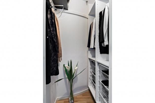 Praktisk klädkammare med lådor och hängare.
