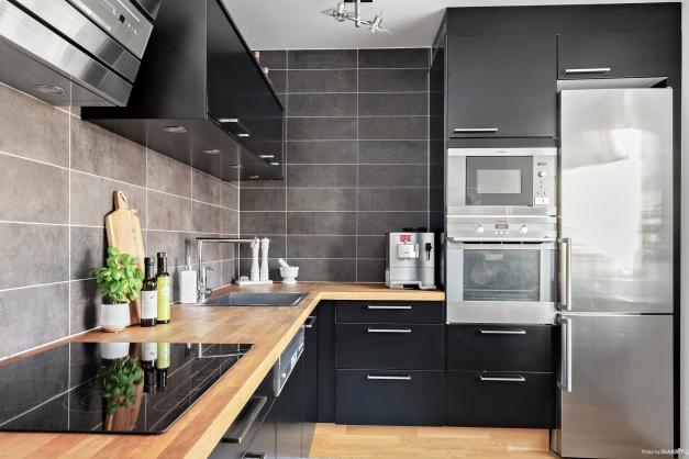 Kök med svarta luckor och rostfria vitvaror.