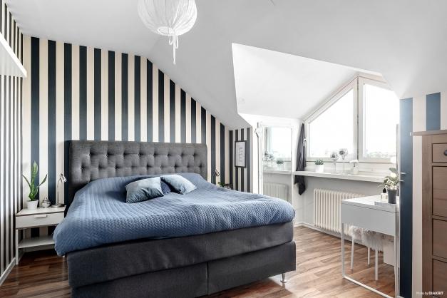 Sovrummet med rogivande tapet samt två inbyggda garderober. De spännande takvinklarna finner du även här.