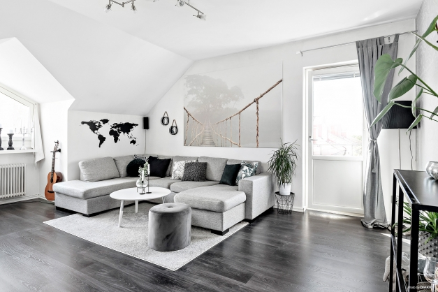 Rymligt vardagsrum med laminatgolv och utgång till balkong.