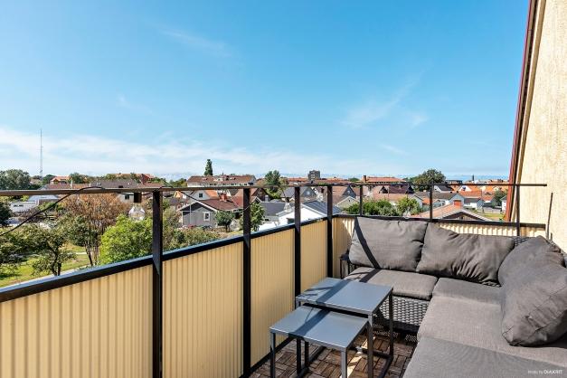 Balkong med klickgolv i trä och fantastisk utsikt över villaområdet. Plats för litet bord, stolar och loungegrupp.