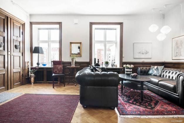 """Vardagsrummet har viss """"studiokänsla"""" då trapphuset leder direkt in i det pampiga rummet via de vackra spegeldörrarna"""