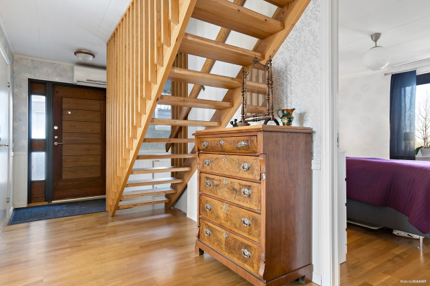 Rymlig hall med trappa till ovanvåningen