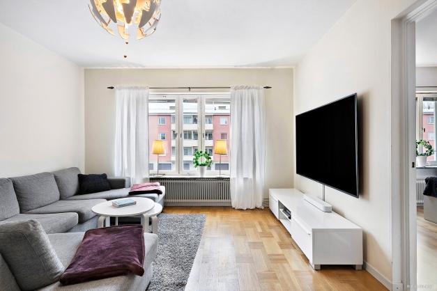 Stort vardagsrum med utrymme för både soffa och matplats