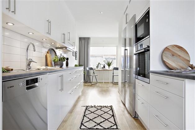 Det eleganta köket kommer från Ballingslöv, färdigutrustat med spishäll, diskmaskin och utdragbar spisfläkt. Kyl, frys samt en inbyggnadsugn och -mikro är anordnade separat och utgör samtidigt en naturlig rumsavdelare.
