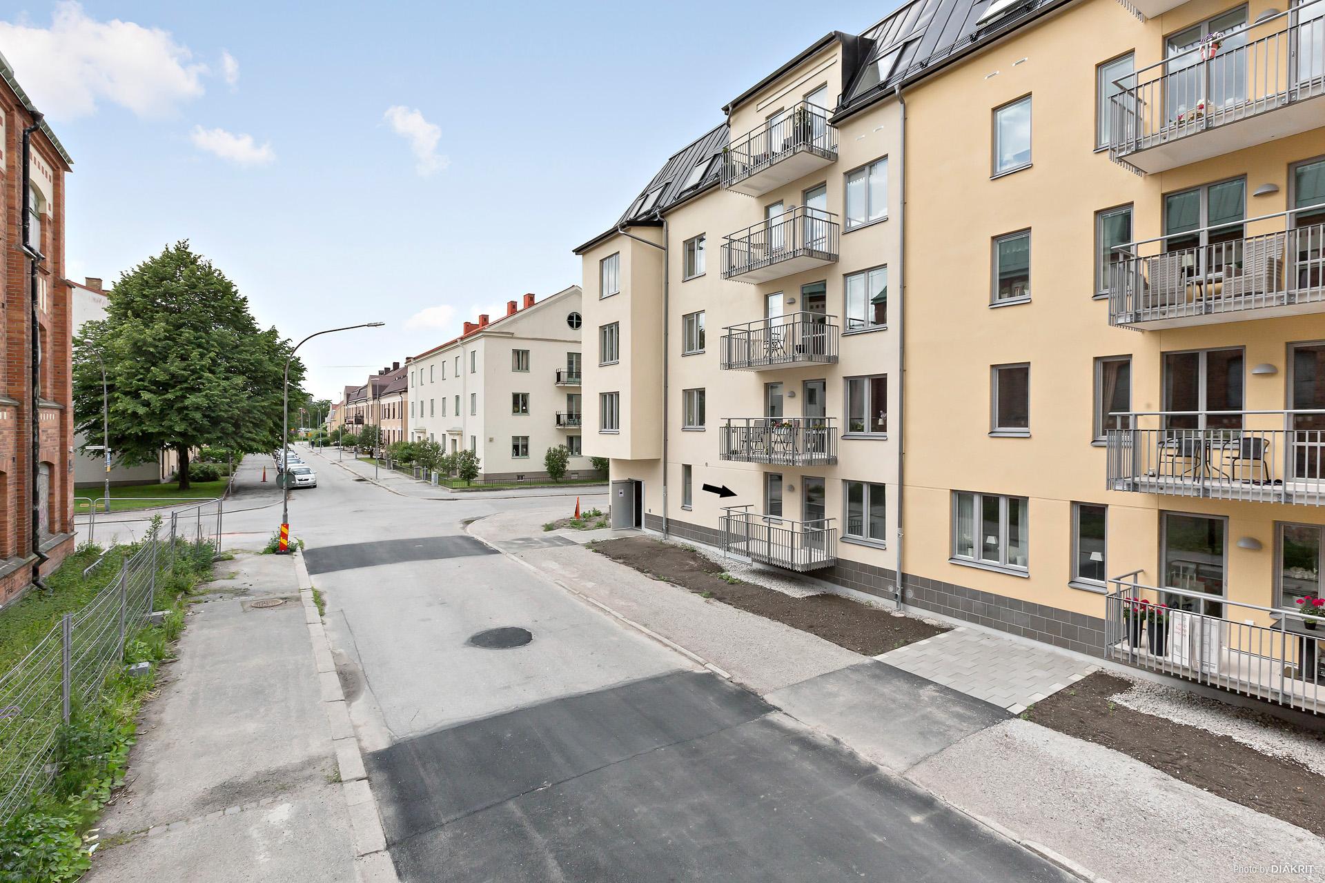 Våning 1 av 5 - balkong mot Rostagatan och stenlagd uteplats mot innergård.