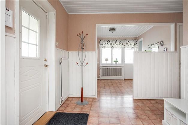 Rymlig hall med flera garderober, utgång till inglasade uterummet, uppgång till övervåningen och nedgång till källaren.