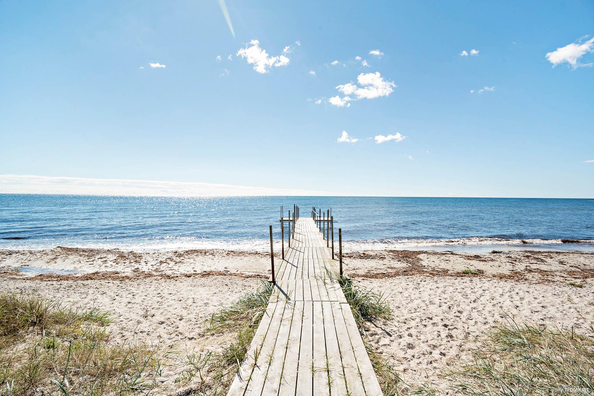 Strand och brygga strax nedanför tomten.