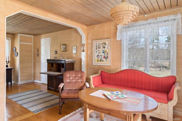 Ljust vardagsrum med öppning mot rummet intill