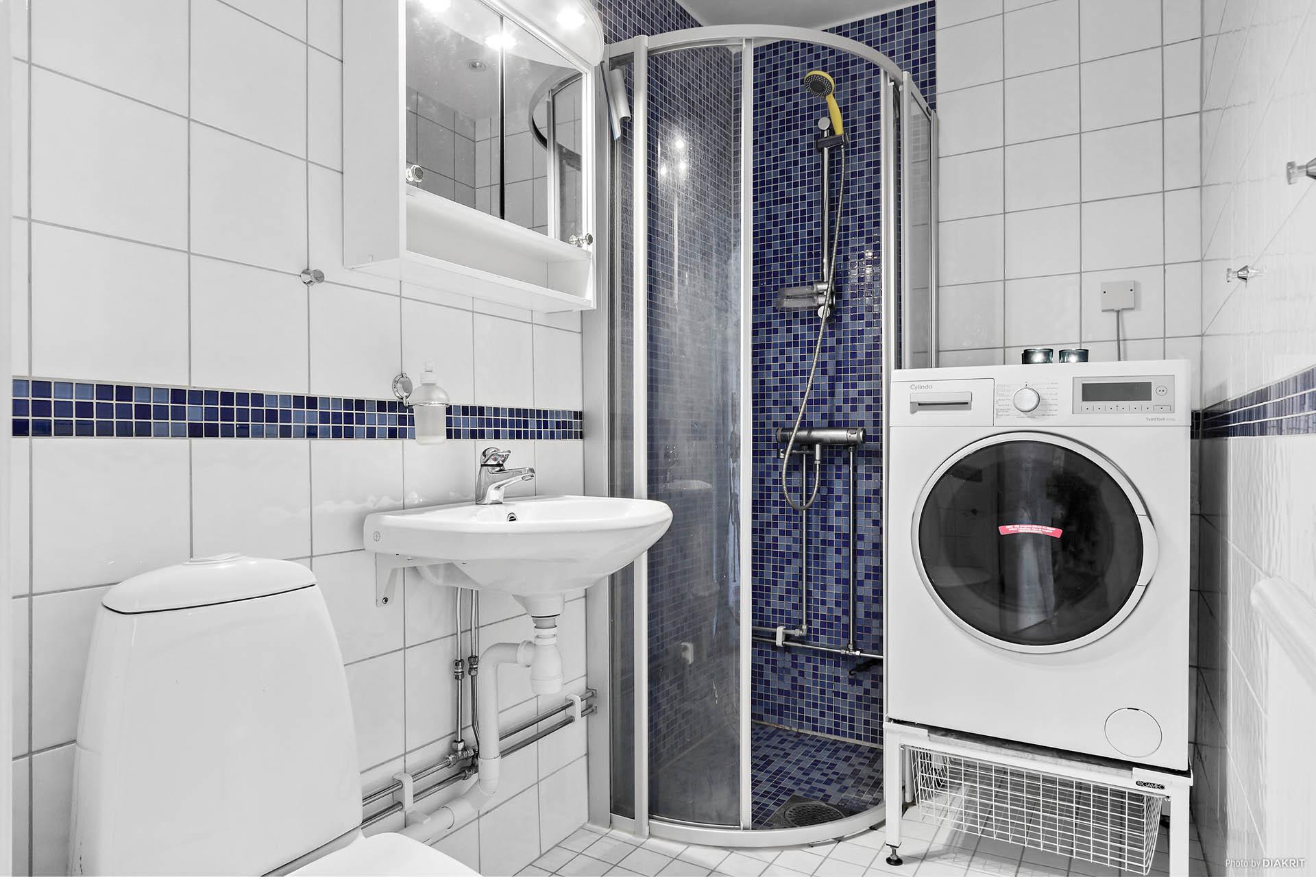 Duschrum med klinkers och kakel. Tvättmaskin med tumlarfunktion