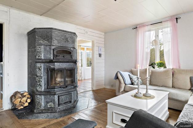Vardagsrum med fint trägolv och rejäl täljstensspis med ugn