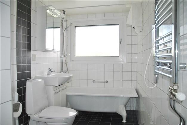 Badrum med klinkergolv och kaklade väggar i neutrala färgval