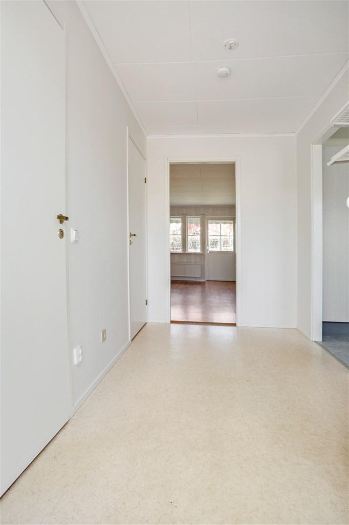 Hall med öppning mot kök och vardagsrum.