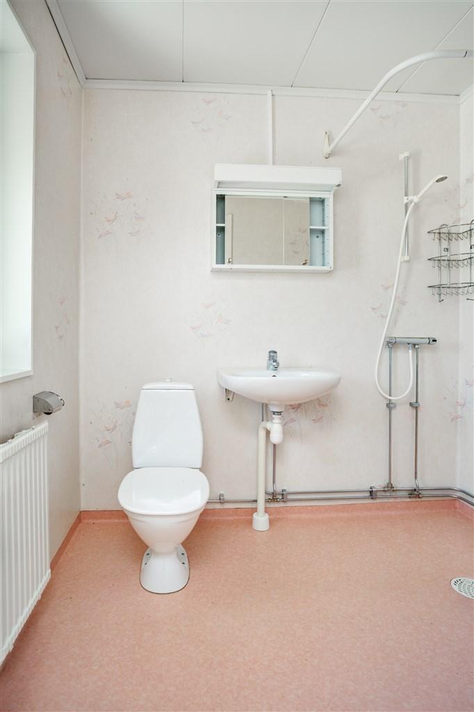 Dusch/wc med plastmatta på golv och vägg.