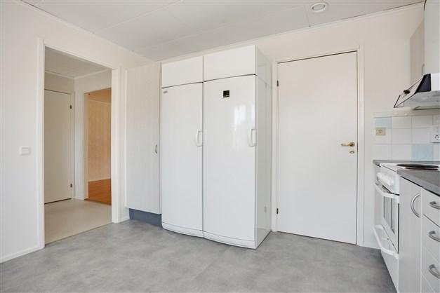 Kök med portal mot hall och ingång till tvättstugan.
