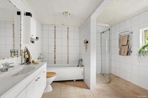 Badrummet är stort som en spaavdelning med både dusch och badkar.