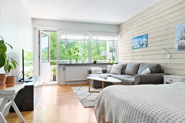 Ljust vardagsrum med plats för soffa och sängavdelning.