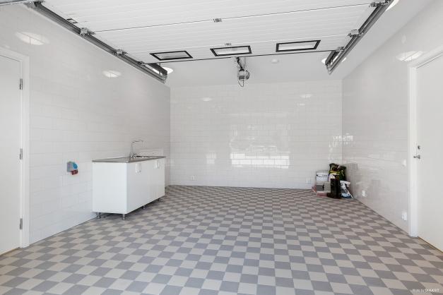 Helkaklat garage med stor fjärrstyrd garageport med en känsla av lyx