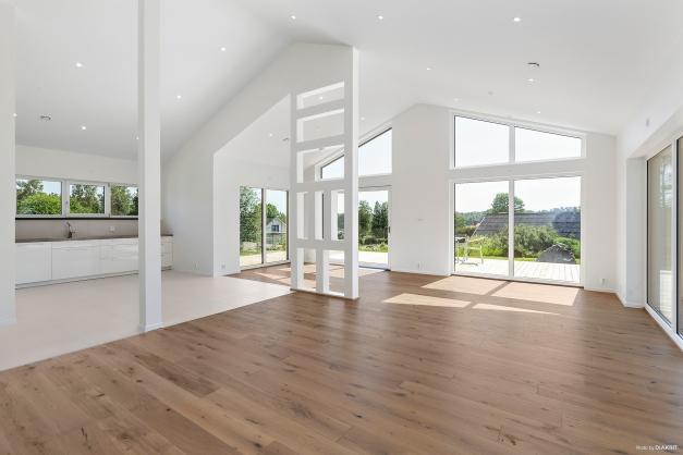 Vardagsrum med öppning till nacknock samt stora förnsterpartier  som skapar både ljus och rymd