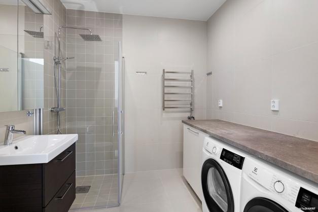 Helkaklat badrum med plats för egen klädvård med tvättmaskin och torktumlare (Electrolux)