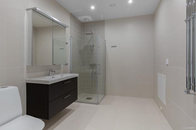 Stort helkaklat badrum för den privata delen i nära anslutning till samtliga sovrum
