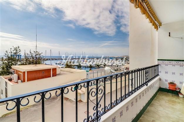 Balkong med utsikt över småbåtshamn och hav