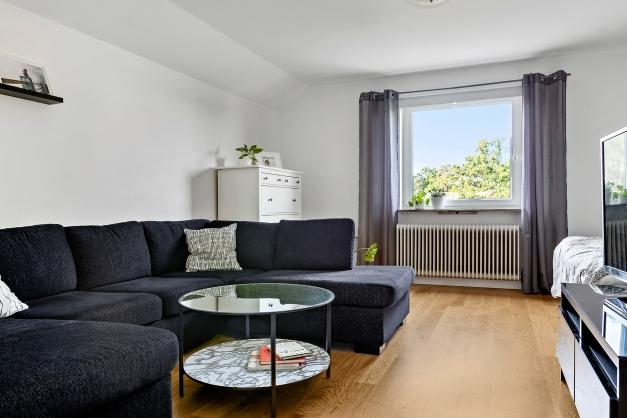 Rymligt vardagsrum med fönster i väster, snedtakskaraktär och sovalkov